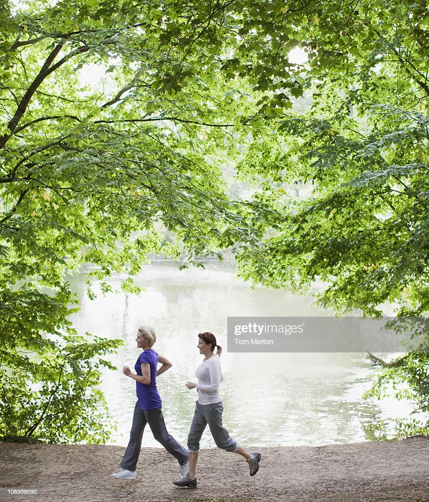 Women jogging together near lake : Stock Photo