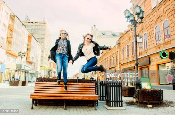 Women jumping for joy near bench