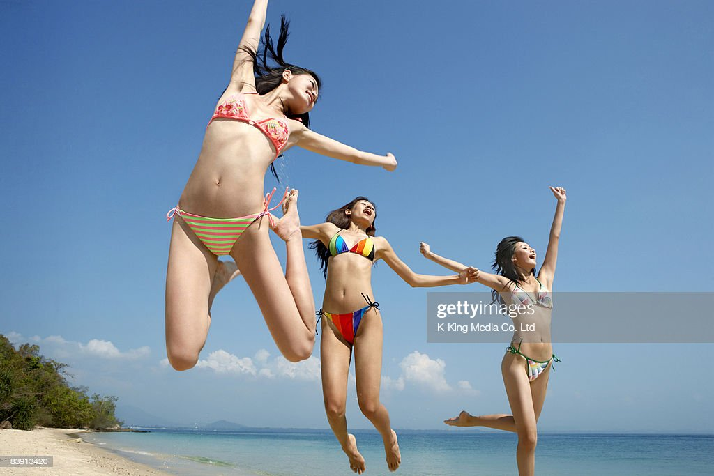 Women jumping in air on beach. : Stock Photo