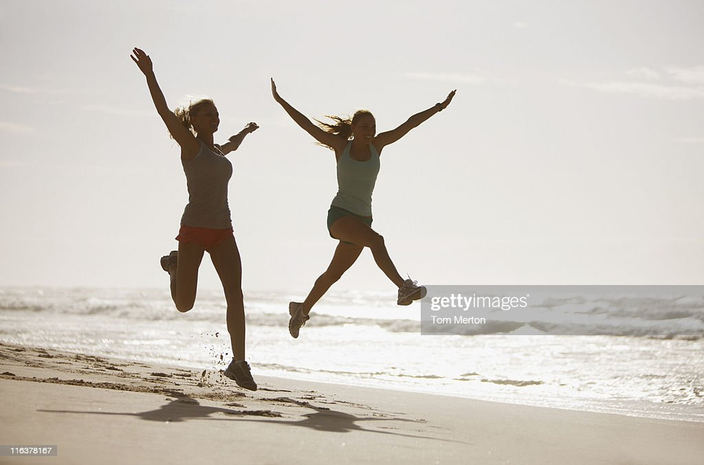 Women jumping on beach : Stock Photo