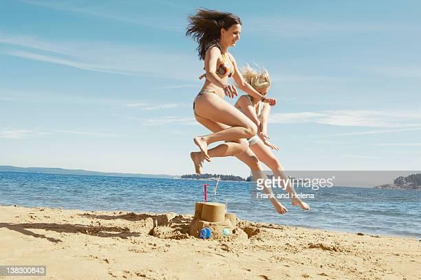 Frauen springen über sandcastle