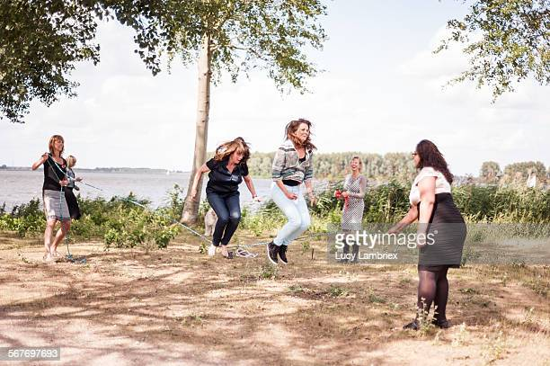 Women jumping rope by the water
