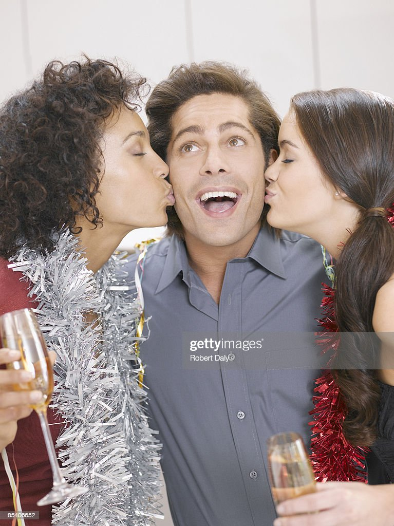 Women kissing man at Christmas party : Stock Photo