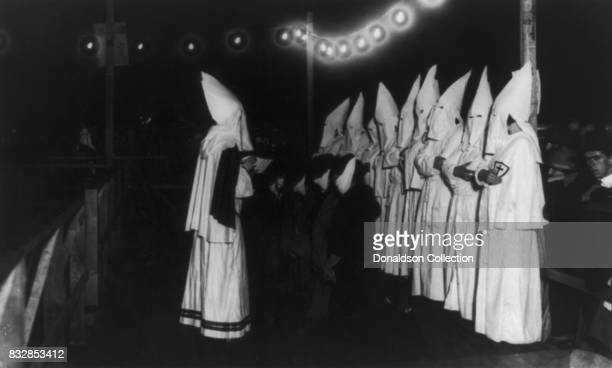 Women kneeling in front of strouded Klansman of the Ku Klux Klan reading from a book other Klansmen stand behind them on the platform spectators...
