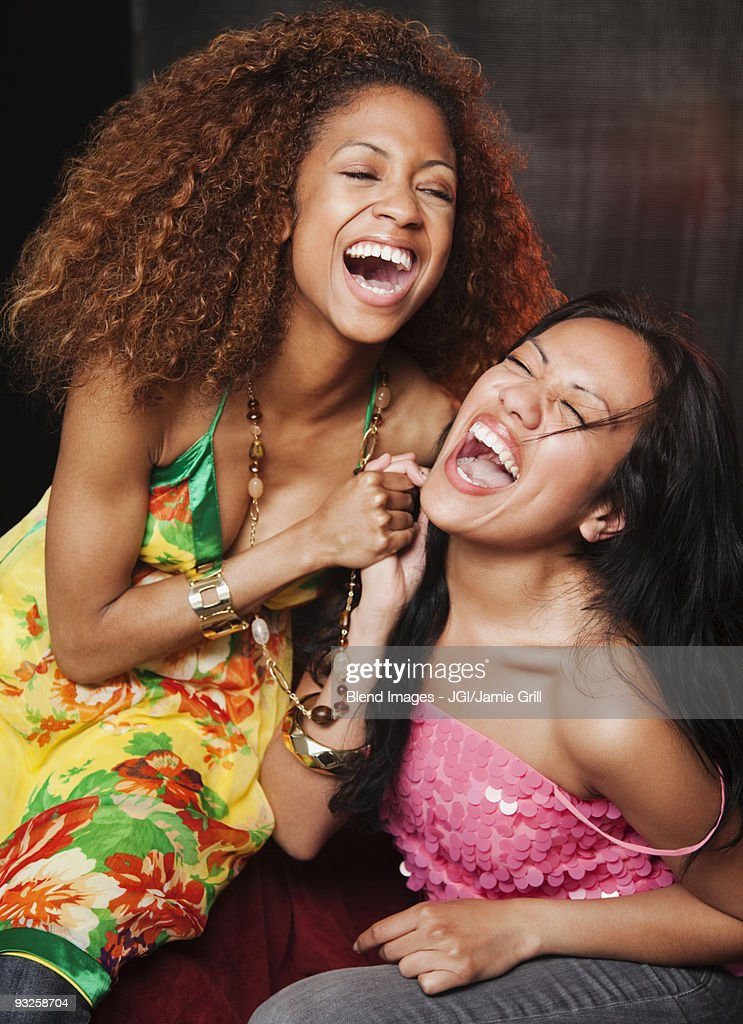 Women laughing and holding hands at nightclub : Stock Photo