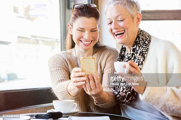 Women laughing at photos on phone in cafe.