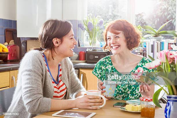 Women laughing having coffee in kitchen.