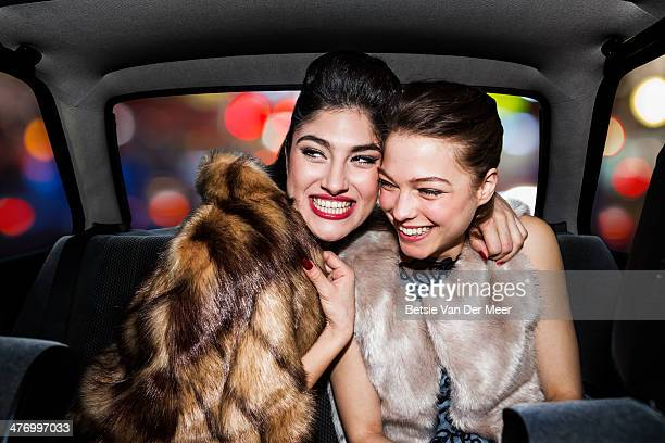 Women laughing in back of car, going out at night.