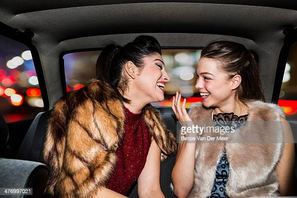 Women laughing in back of car, going out.