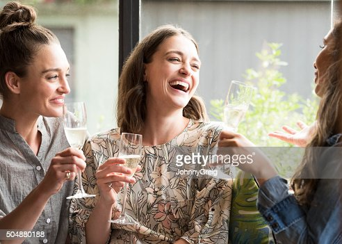 Women laughing in bar with wine glasses
