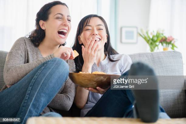 Women laughing on sofa together