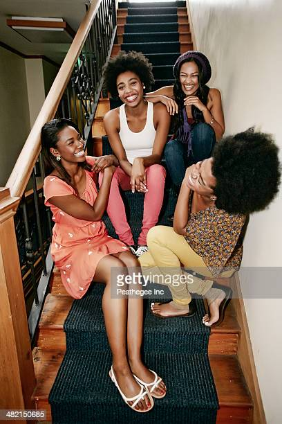 Women laughing on steps in apartment building
