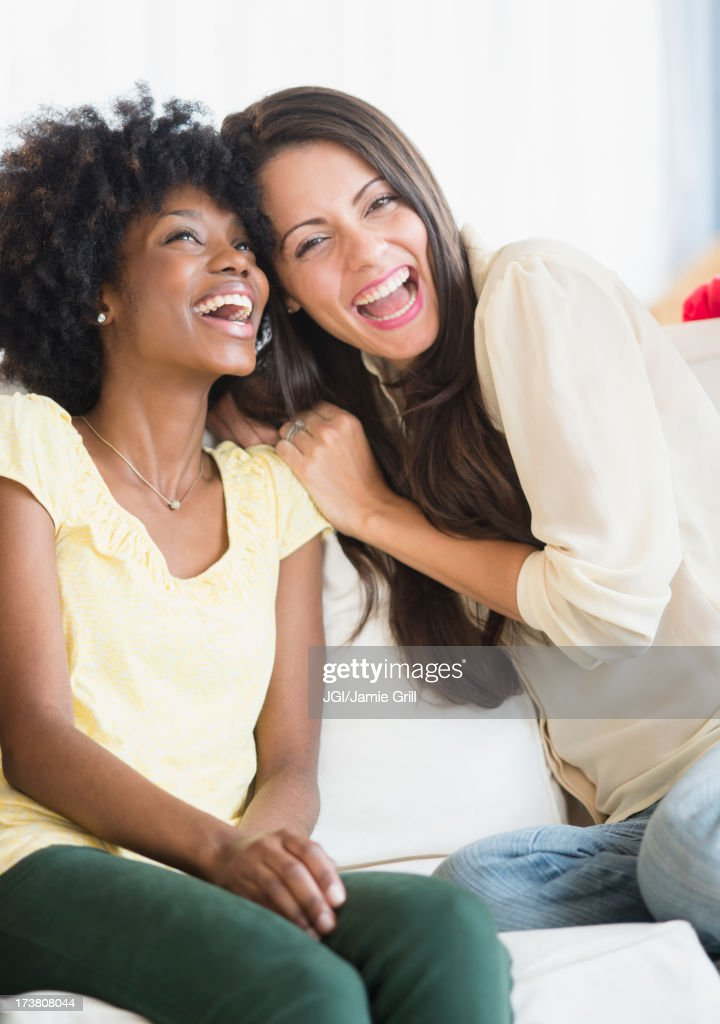 Women laughing together on sofa : Stock Photo