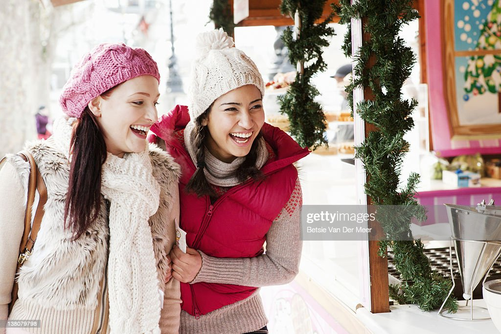 Women laughing waiting for pancakes at stall. : Stock Photo