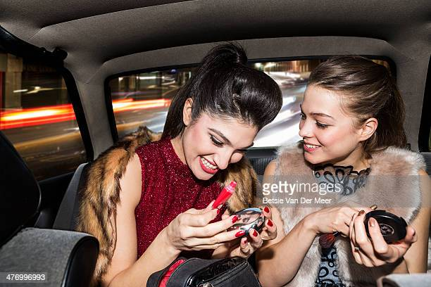 Women laughing while touching up make up in car.