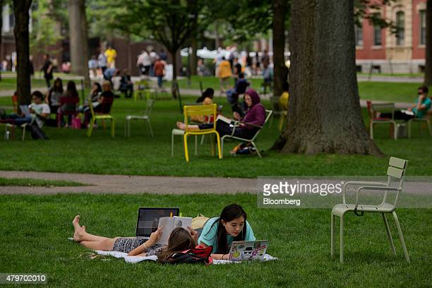 Women lay in the grass of Harvard Yard at the Harvard University campus in Cambridge Massachusetts US on Tuesday June 30 2015 Harvard University...