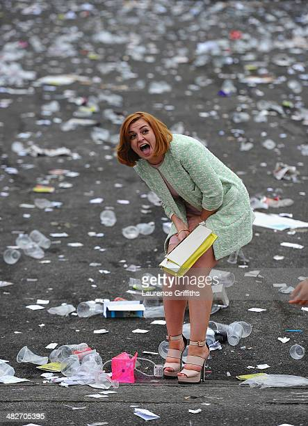 Women leave after the final race amongst the debris left behind at Aintree Racecourse on April 4 2014 in Liverpool England