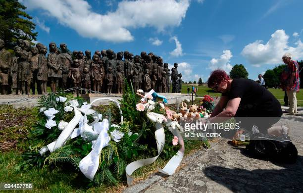 A women light a candles on at the memorial dedicated to the local children who perished in Nazi concentration camps on June 10 2017 in Lidice village...