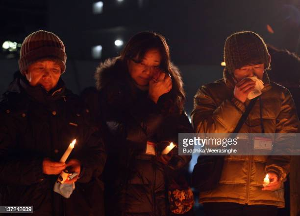 Women light candles and pray during the Kobe Great Earthquake during a memorial ceremony to commemorate the 17th anniversary of the 1995 Great...