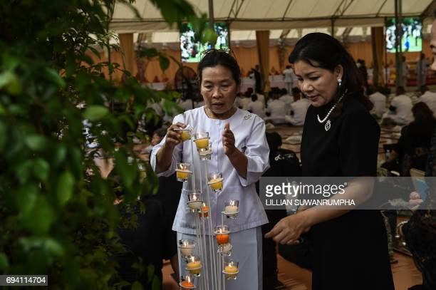 Women light candles before a Buddhist ceremony in honour of the late Thai King Bhumibol Adulyadej at the King Rama V Monument in Bangkok on June 9...