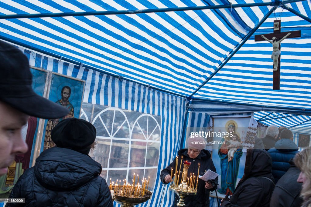 Women light candles in a tent serving as a chapel on Independence Square on February 23, 2014 in Kiev, Ukraine. After a chaotic and violent week, Viktor Yanukovych has been ousted as President as the Ukrainian parliament moves forward with scheduling new elections and establishing a caretaker government.