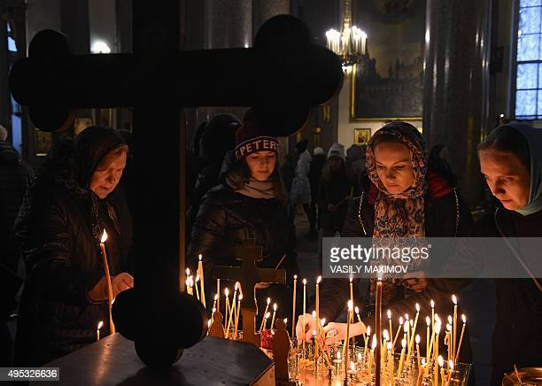 Women light candles in Kazansky Cathedral in StPetersburg on November 2 in memory of the victims of a jetliner crash Russian airline Kogalymavia's...