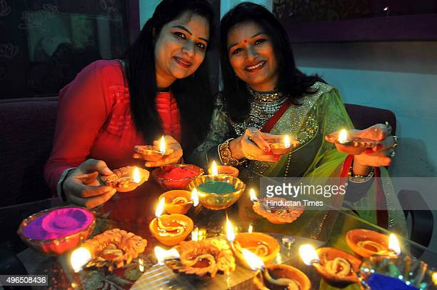 Women lighting diya lamps and enjoying Diwali festivities on November 10 2015 in Indore India Festival of light Diwali is one of the most important...