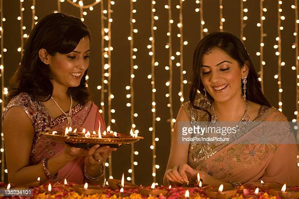 Women lighting diyas