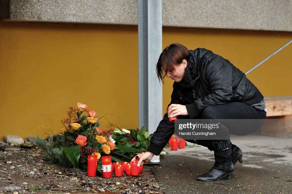 A women lights a candle at a Caritas employment facility for the handicapped where a fire killed 14 people on November 27 2012 in TitiseeNeustadt...