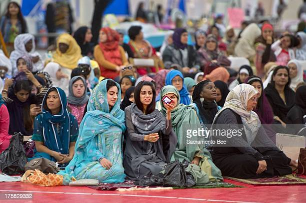 Women look at a picture they took of themselves before the start of the Eid prayer marking the end of Ramadan the Muslim monthlong fasting ritual as...