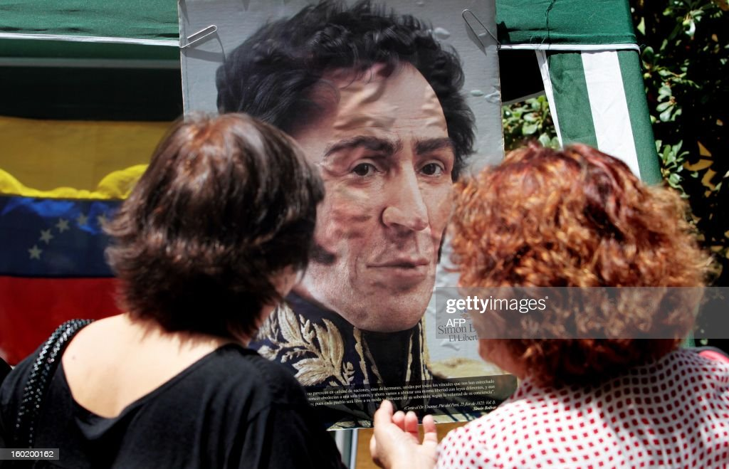 Women look at a poster of Latin American independence hero Simon Bolivar during the People's Summit being held in Santiago in the sidelines of the Latin American and Caribbean States (CELAC)-European Union (EU) Summit, on January 27, 2013. European and Latin American leaders have pledged to shun protectionism and boost their strategic partnership to foster free trade and sustainable development based on close international cooperation. Some 60 countries are represented at the summit between the 27-member European Union and the Community of Latin American and Caribbean States, or CELAC. AFP PHOTO / RODRIGO SAENZ