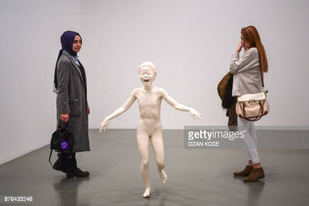 Women look at a statue by Algerian artist Adel Abdessemed recreating the photo 'Napalm Girl' during the 15th Istanbul Biennial on November 3 2017...