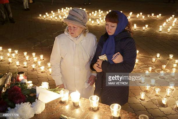 Women look at candles and flowers in Simferopol on November 1 2015 in memory of the victims of a jetliner crash Russia mourned its biggest ever air...