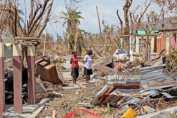 Women look at destruction on a street near Port Salut Haiti on October 9 2016