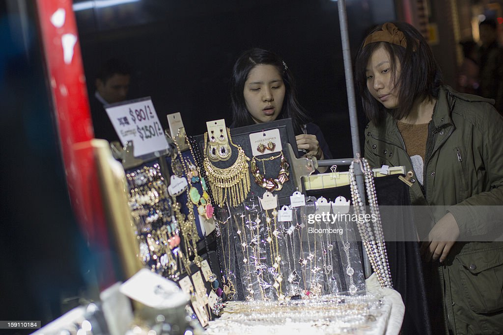 Women look at jewelry displayed for sale at a street stall in Hong Kong, China, on Friday, Jan. 4, 2013. Chief Executive Leung Chun-ying, who has been buffeted by student protests and low popularity since taking office on July 1, has pledged to tackle Asia's biggest wealth gap as the division between poor and rich widened to its worst level since at least 1971. Photographer: Jerome Favre/Bloomberg via Getty Images
