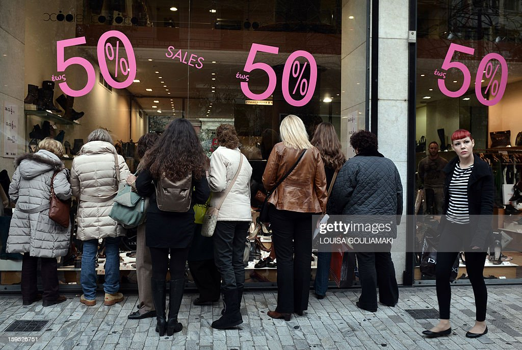 Women look at offers in a shoe shop in central Athens, on the first day of the winter sales in Greece on January 15, 2013. The eurozone will shortly clear the next slice of bailout funding for Greece worth 9.2 billion euros, with Athens satisfying conditions for the payment, EU sources said on Tuesday. AFP PHOTO/ Louisa Gouliamaki