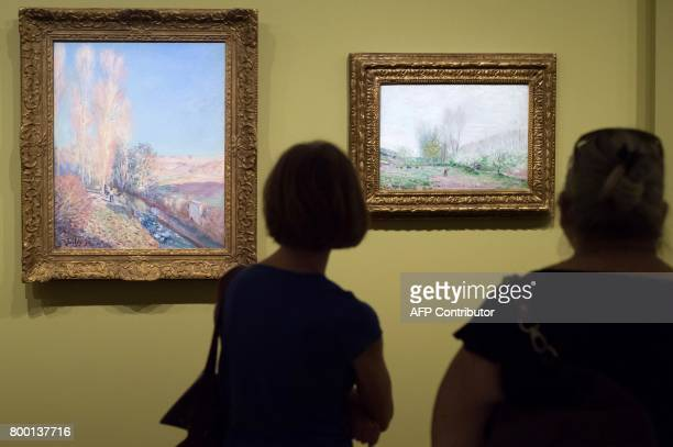 Women look at paintings entitled 'Ete de la SaintMartin' and 'Les Pommiers en fleur' by late French painter Alfred Sisley as part of the exhibition...