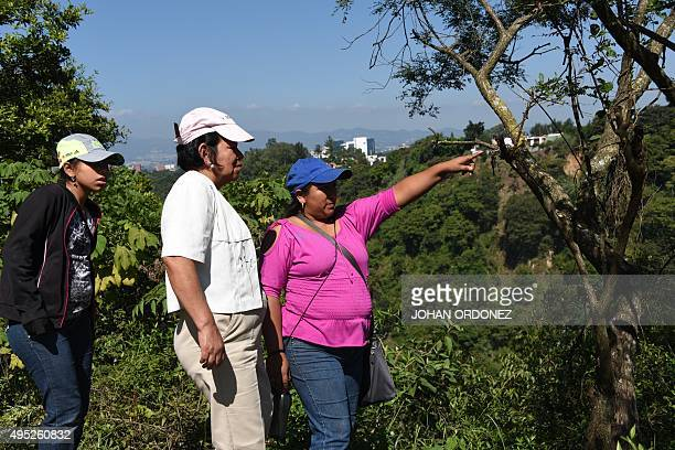 Women look at the site of past October 1 landslide in the village of El Cambray II Santa Catarina Pinula municipality some 15 km east of Guatemala...