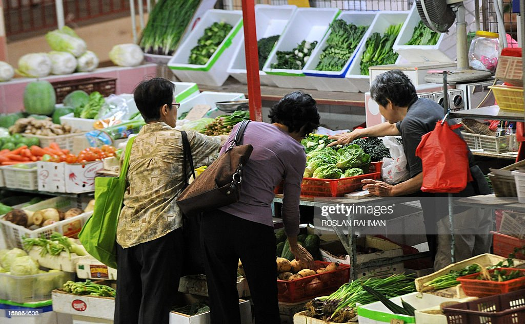 Women look at vegetables at a market in Singapore on January 2, 2013. Singapore's economy grew in the fourth quarter, avoiding a technical recession despite disappointing growth figures for 2012, government data showed on January 2. AFP PHOTO / ROSLAN RAHMAN