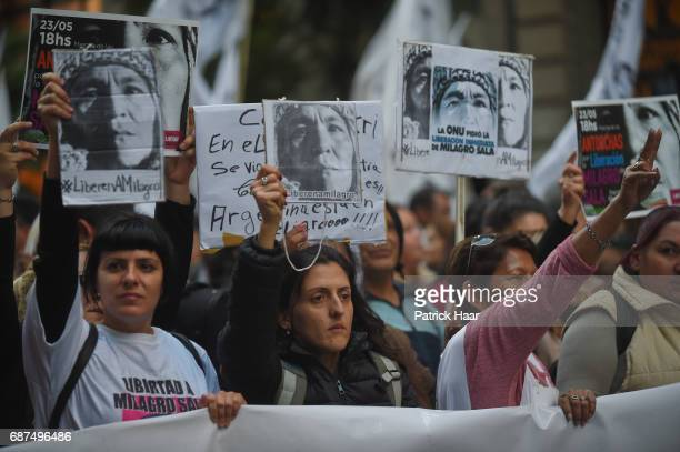 Women look on and hold signs with the face of Milagro Sala as part of a demonstration to demand freedom for the leader of Tupac Amaru Organization...