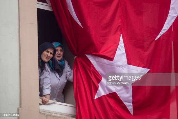 Women look out a window covered by a Turkish flag while listening to Kemal Kilicdaroglu leader of the CHP speak during a 'Hayir' campaign rally on...