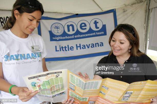 Women looking at a neighborhood enhancement team brochure at Miami River day