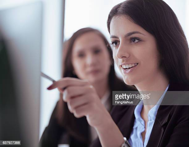 Women looking at computer screen in office