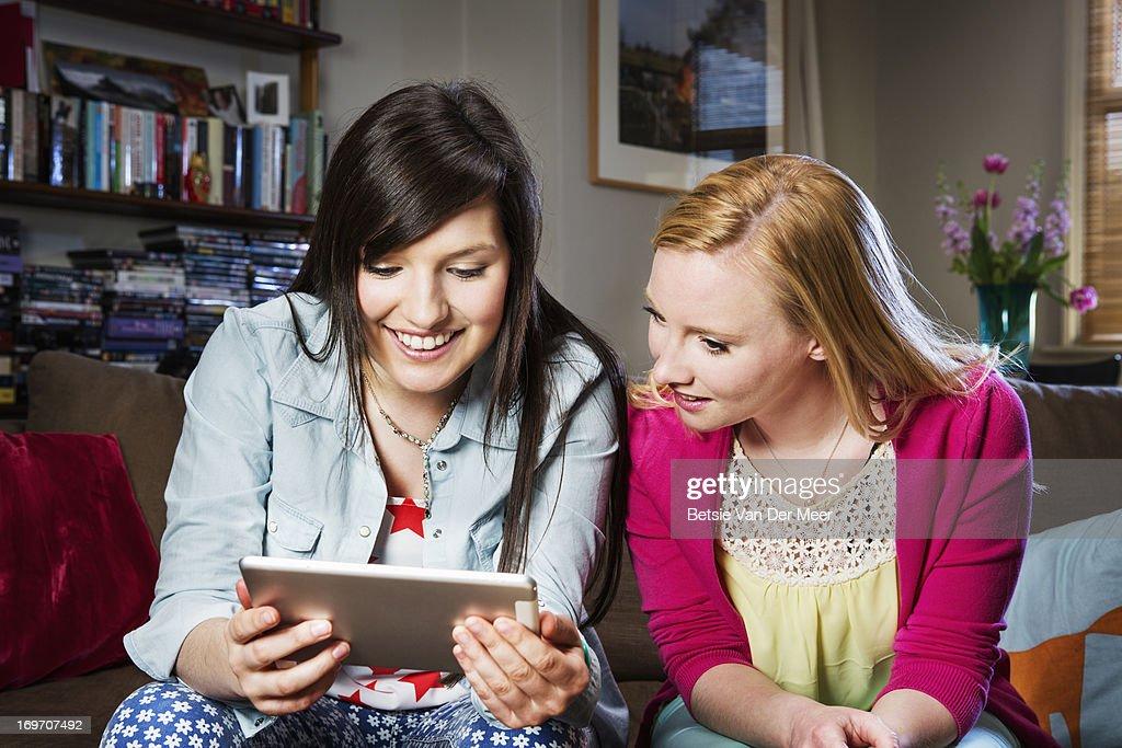 Women looking at digital tablet in livingroom. : Stock Photo