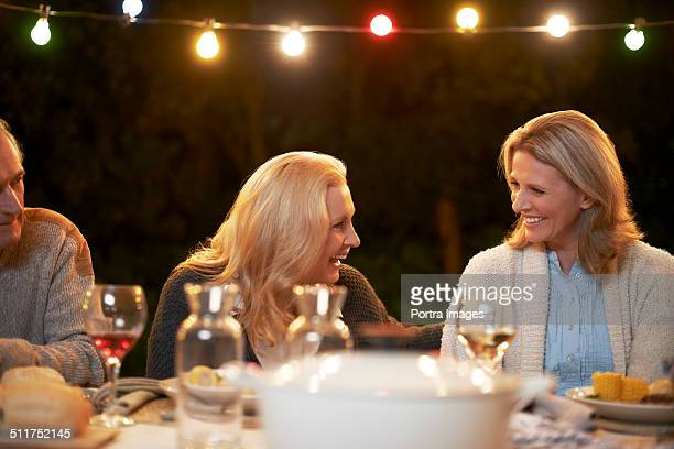Women looking at each other while having food