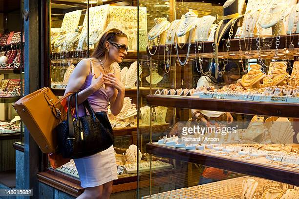 Women looking at gold shop window display on Ponte Vecchio.