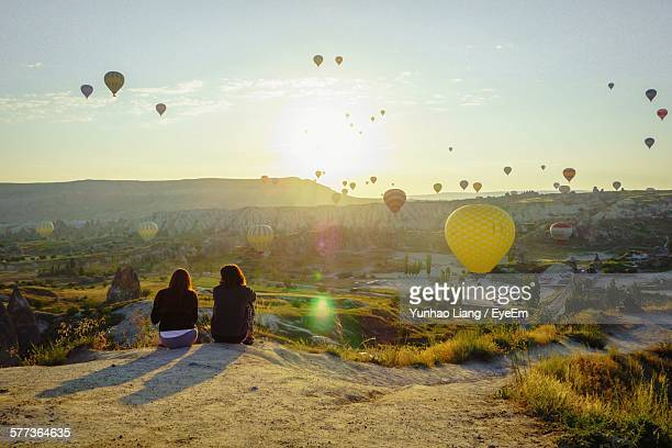 Women Looking At Hot Air Balloons While Sitting On Mountain At Cappadocia