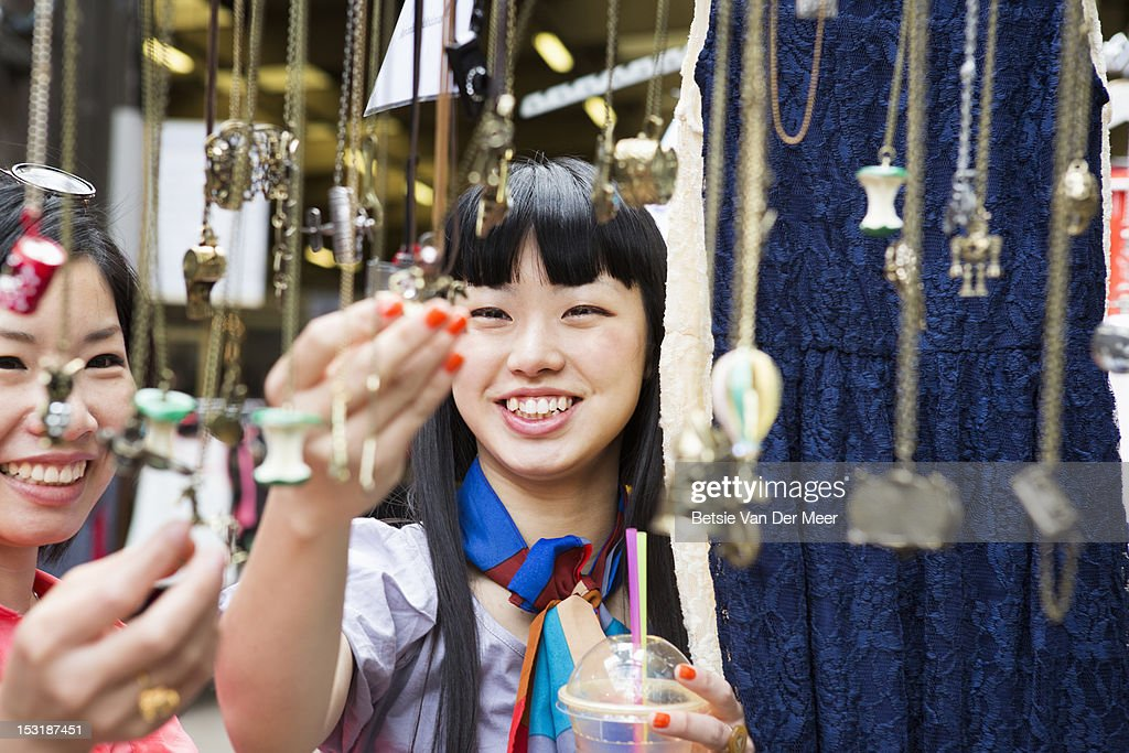 Women looking at jewellery at market stall. : Stock Photo