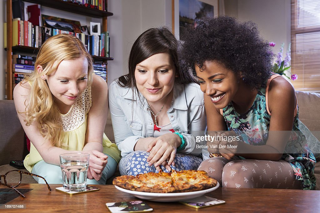 Women looking at large pizza ready to be eaten.