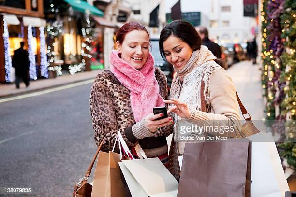 Women looking at mobile phone in street.